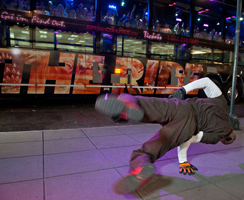 A breakdance balancing on his hand in front of THE RIDE bus in NYC