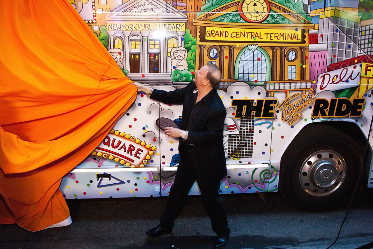 Charles Fazzino pulls a giant orange curtain to reveal his 3D pop art bus, THE Fazzino RIDE